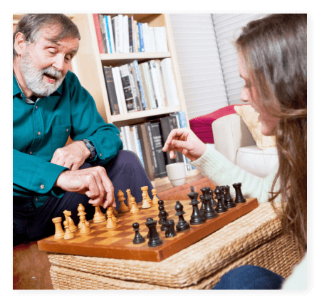 A caregiver and elderly playing chess